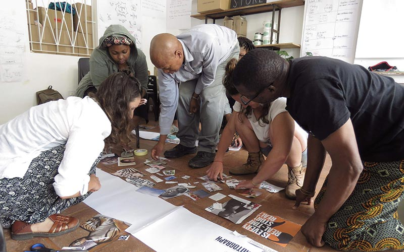 Group of people huddled around images and pieces of paper.