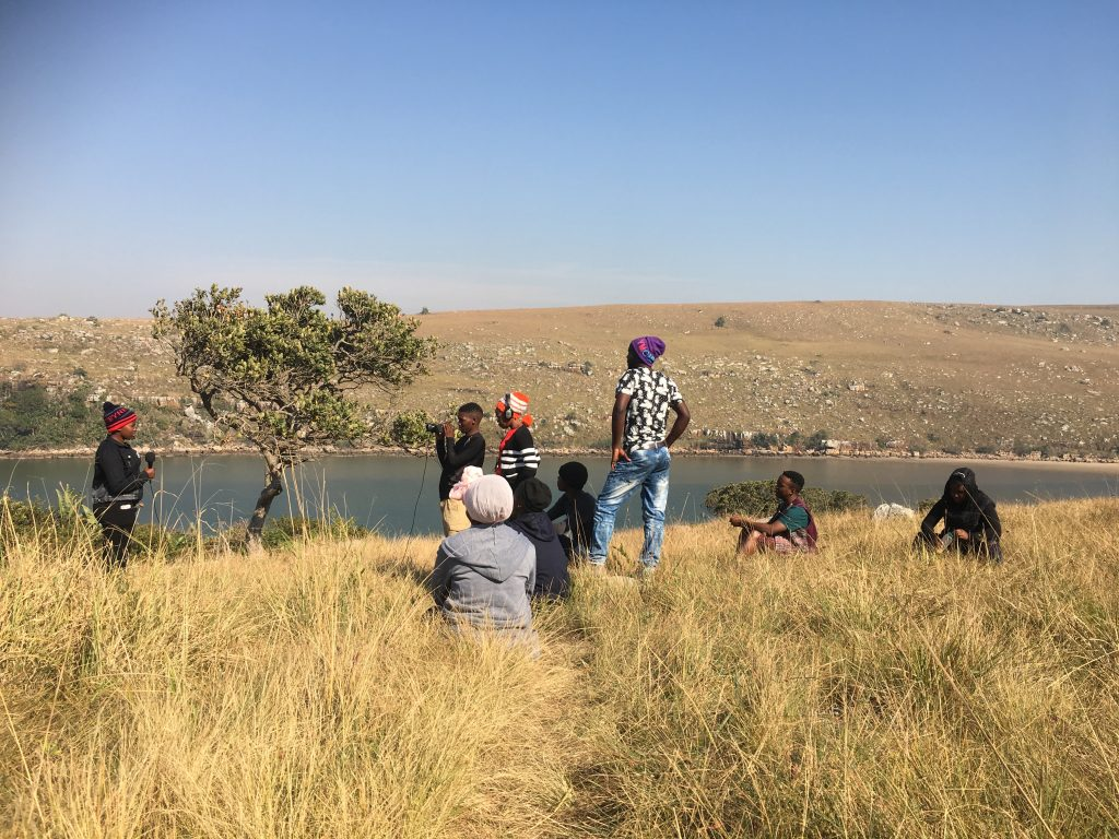 A few people stand on the edge of a dam.