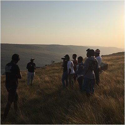 Group of people making a video on a hill side.