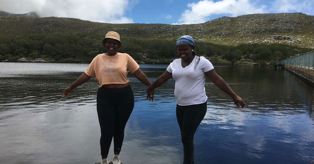 Two women smiling and holding hands in front of a dam with mountains in the background.