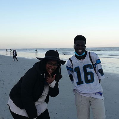 Two people standing on the beach smiling.