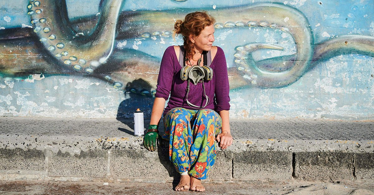 Claire Homewood sitting in front of one of her graffiti murals.