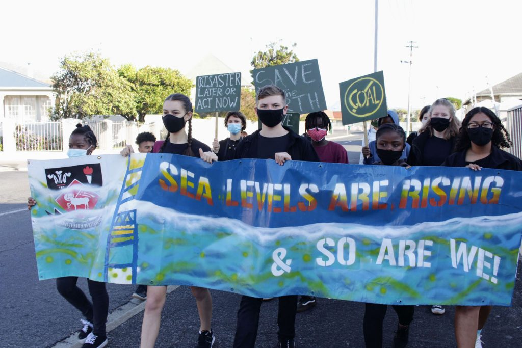 Kids marching with a banner that says 'Sea levels are rising & so are we' taken by Margaret Stone.