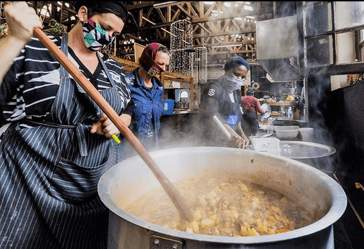 Women stirring large puts of hearty-looking food with big wooden spoons.