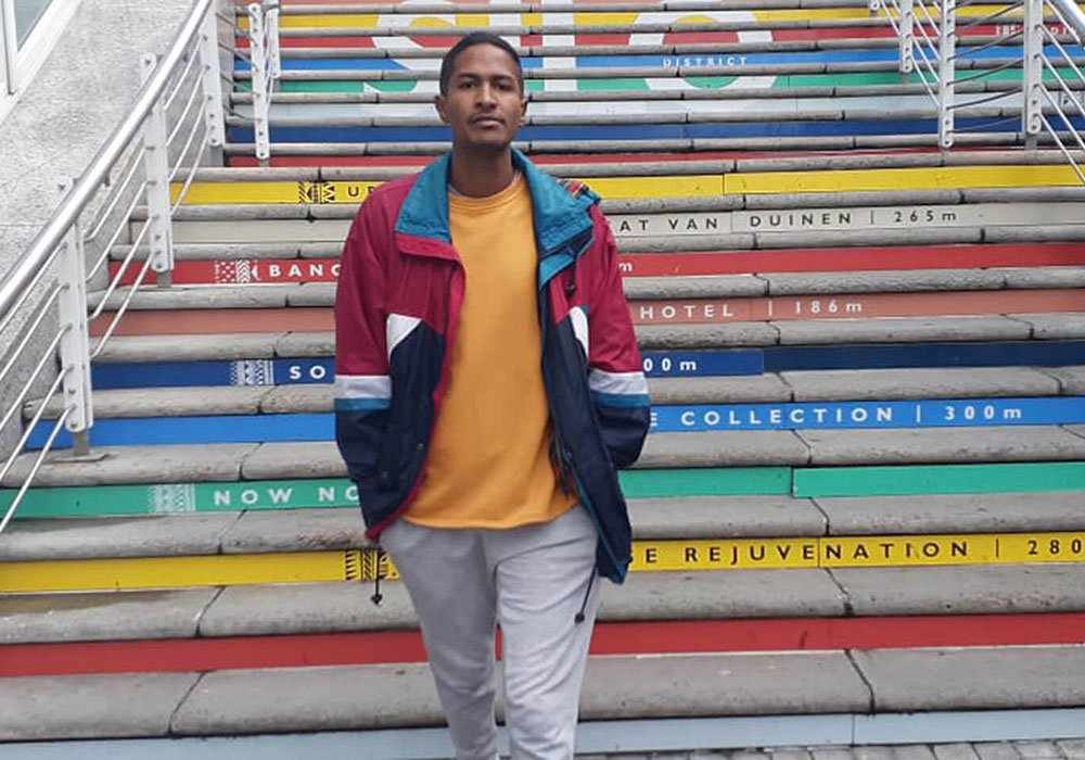 Zubair standing in front of colourful stairs in a yellow shirt with hands in his pockets.