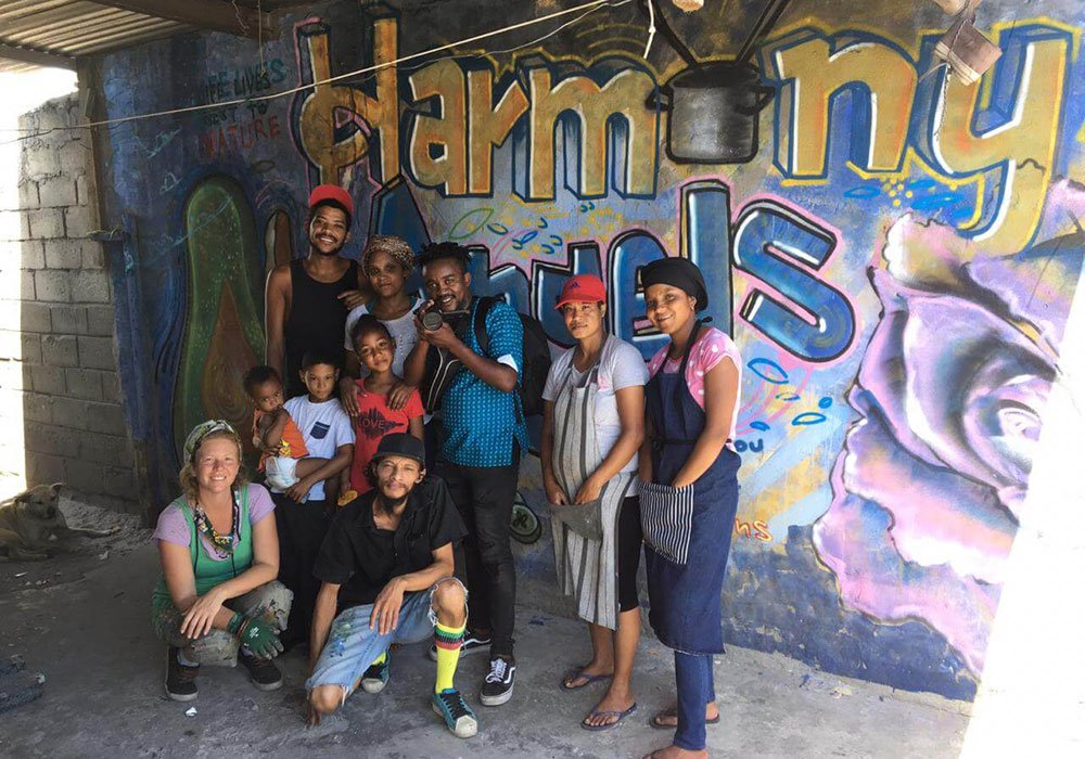 Group of people standing in front of a graffiti mural.