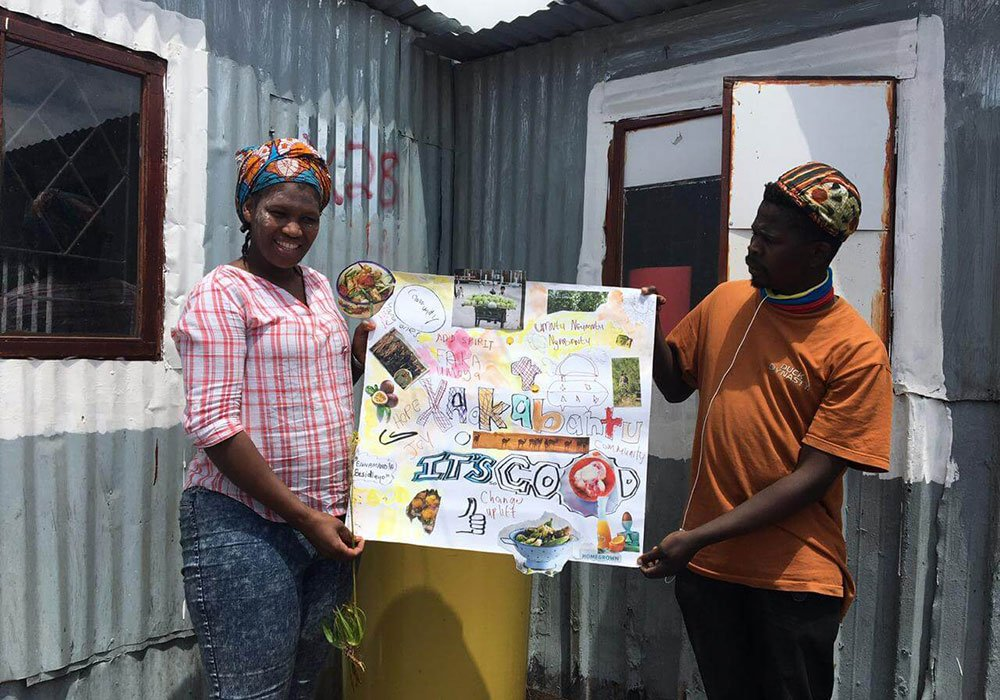 Two people holding up a collage.