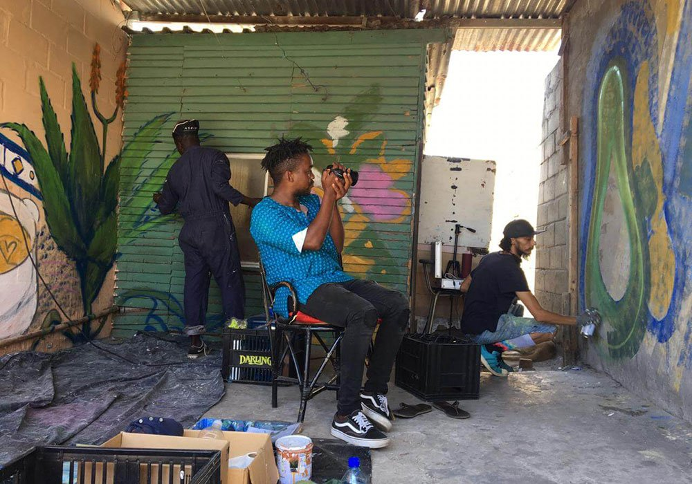 A man sitting on a chair with a camera filming and photographing two other people busy with a graffiti mural.