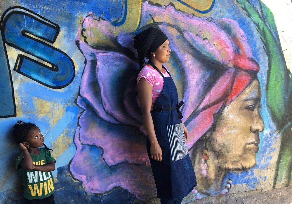 A woman and child stand in front of a colourful graffiti mural.