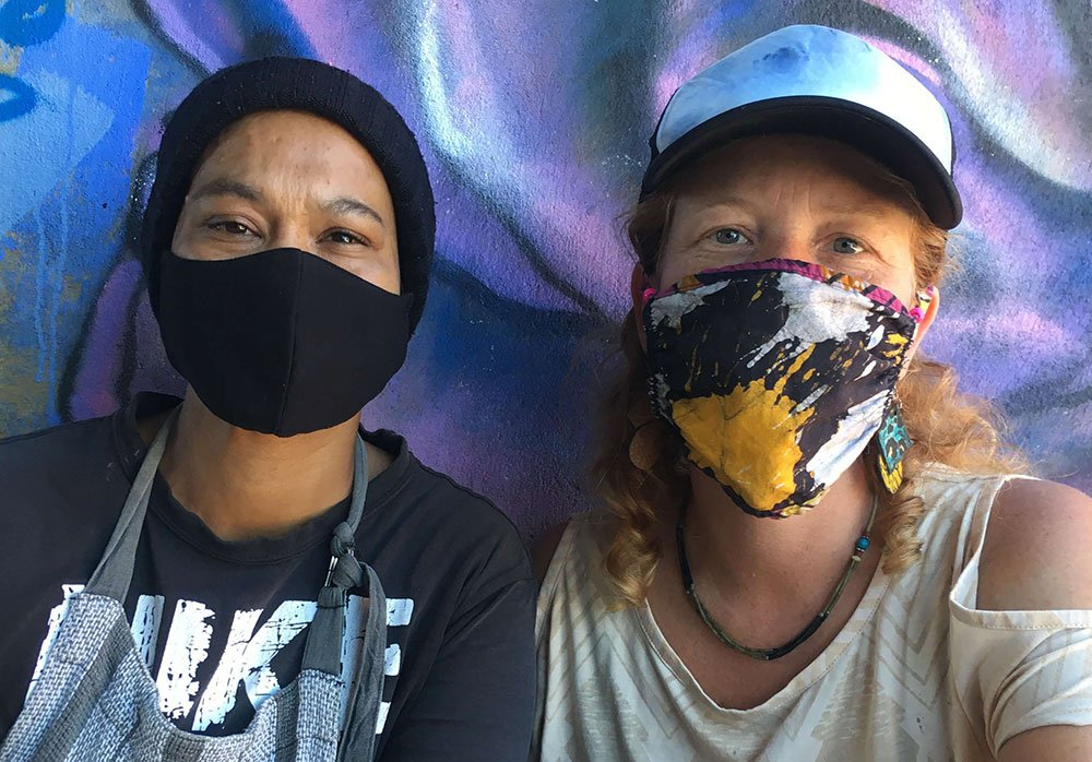 Two woman in masks standing in front of a blue and purple coloured graffiti mural.