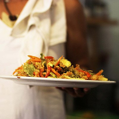 Person holding a full, colourful plate of food.