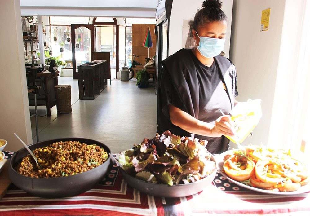 Woman serving food from a number of large colourful serving bowls.