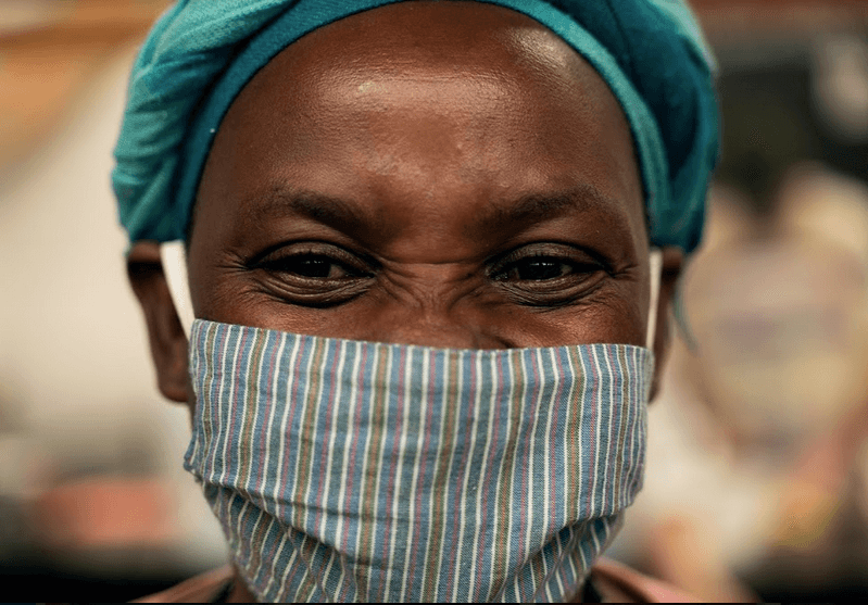 Close up of a woman smiling with a mask on.