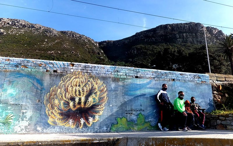 Group of people standing in front of the feather duster worm graffiti mural.