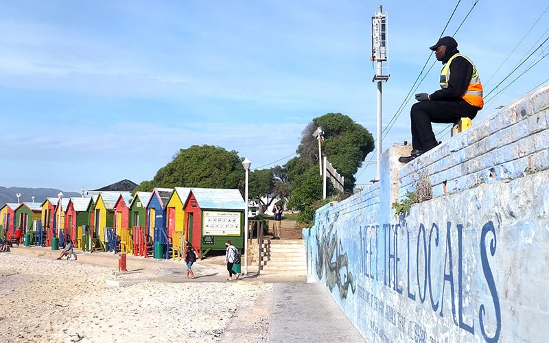 Security guard sitting on the 'meet the locals' mural wall with colourful beach houses in the background.