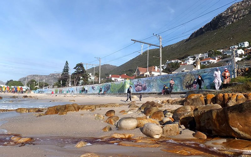 Muizenberg beach with the graffiti mural on a large wall lining the beach.