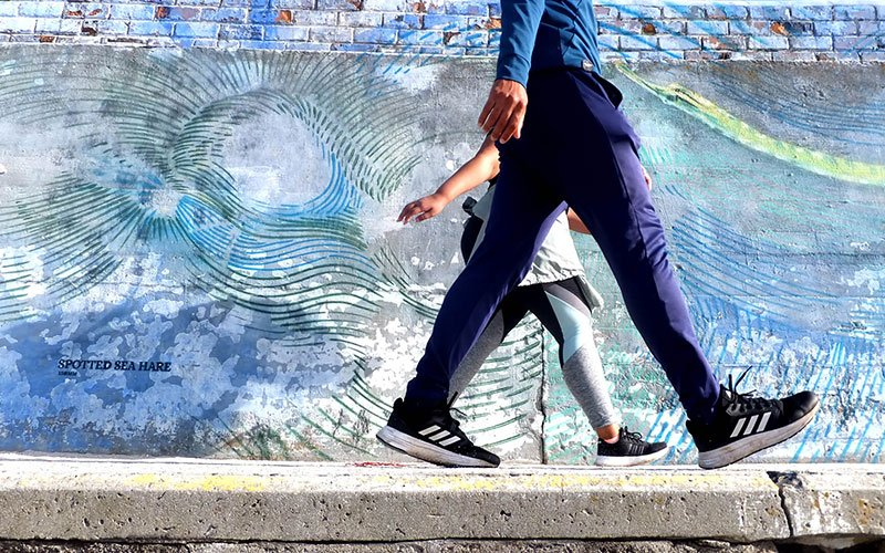 Low angle shot of two people walking past a spotted sea hare graffiti mural.